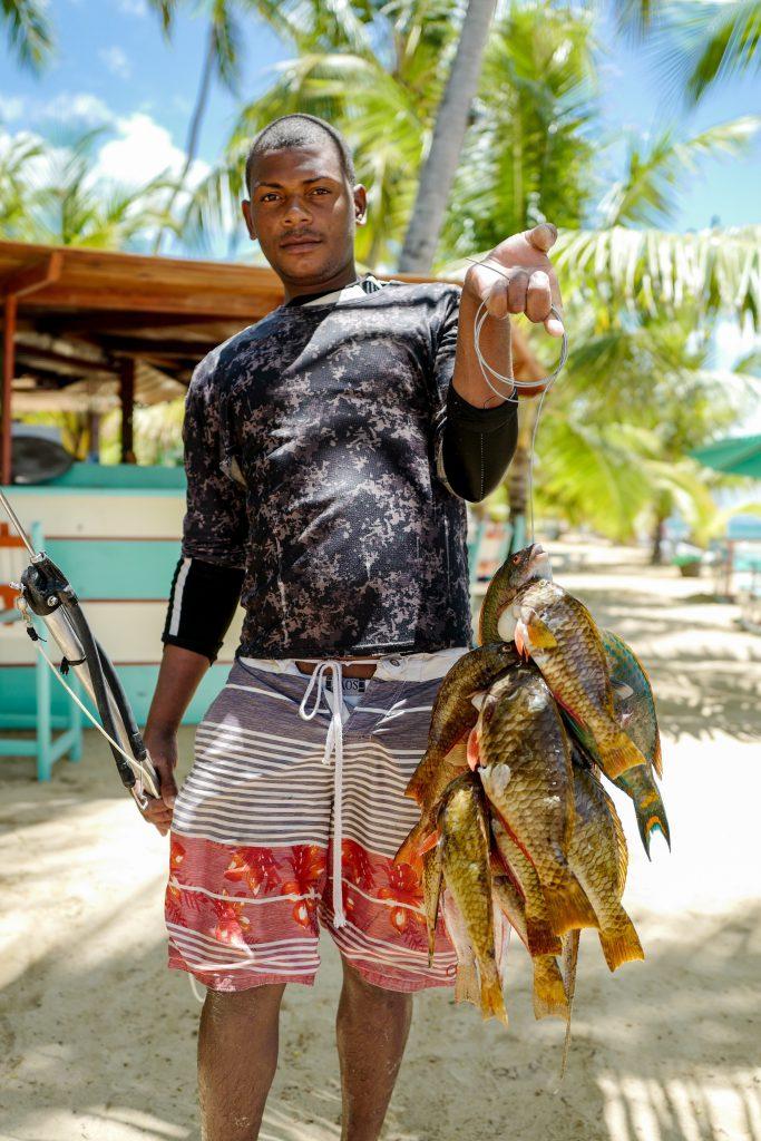 uomo e pesce appena pescato su una costa - fish street food