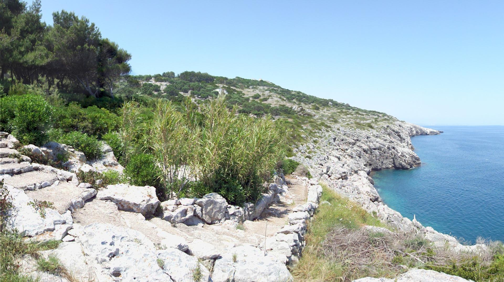 The sea path to comfortable private rock cove with platform and stairs to enter the water
